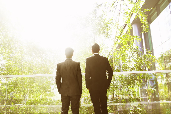 Two businessmen surrounded by trees