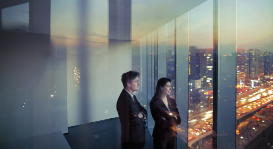 Two business colleagues looking out window in office