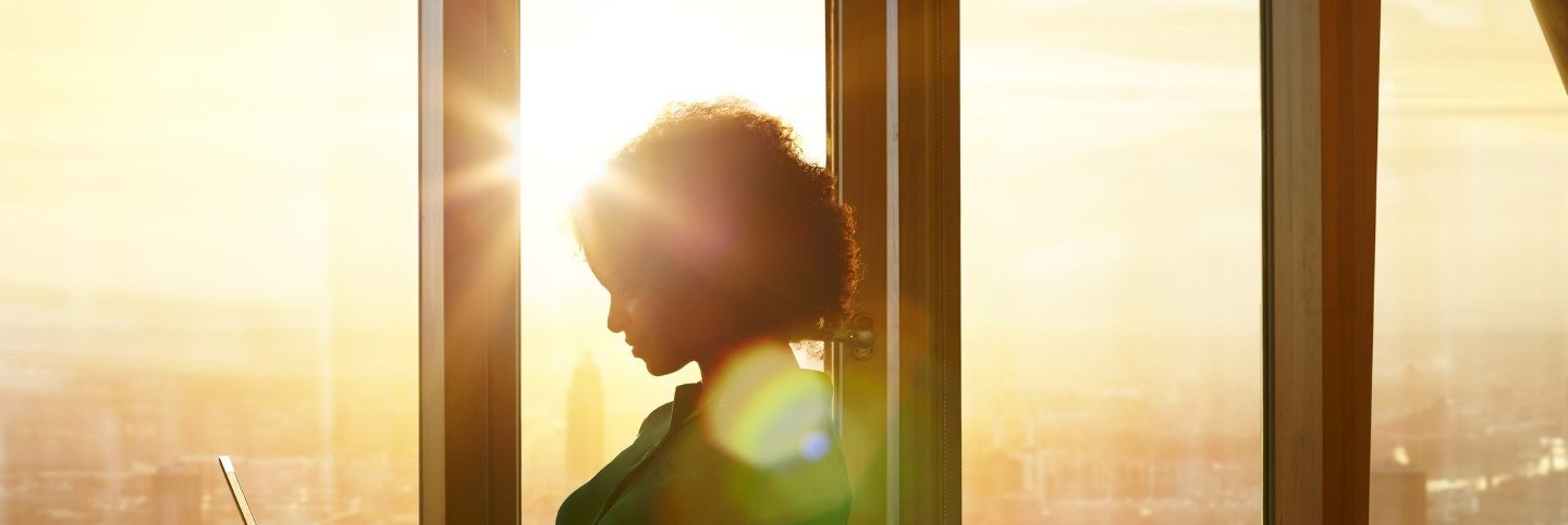 Businesswoman on laptop at window in a sunny morning