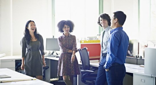 Group of colleagues discussing project in informal meeting in office workstation