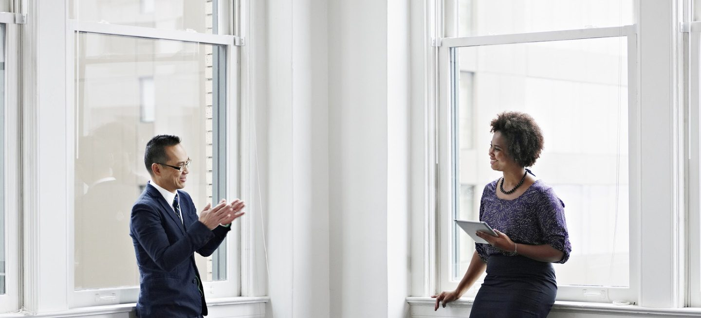 Businesswoman holding tablet and discussing project with businessman in office